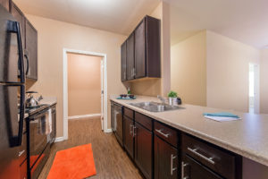Stallion Pointe kitchen with brown cabinets and hardwood floors