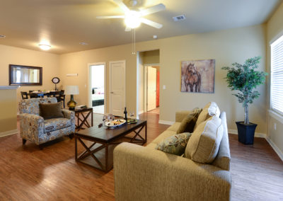Living room with tan couch, brown coffee table, and hardwood floors at Stallion Pointe apartments