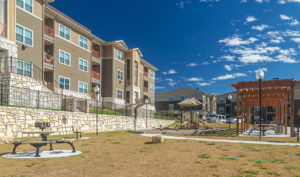 Exterior view of Stallion Pointe apartments with playground and seating area