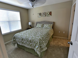 Stallion Pointe master bedroom with queen bed and green comforter