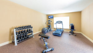 Fitness center at Stallion Pointe with a treadmill, elliptical, stationary bike, racked free weights, and a workout bench