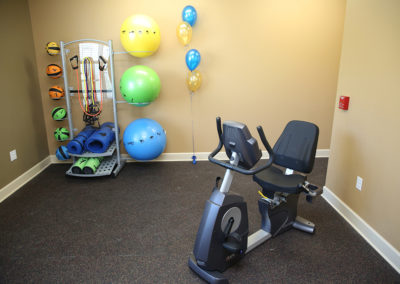 Fitness room at Stallion Pointe with a stationary bike, medicine balls, bosu balls, and workout mats
